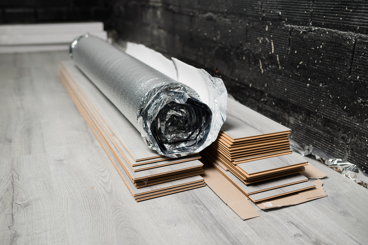 Insulating material roll and laminate floor pieces