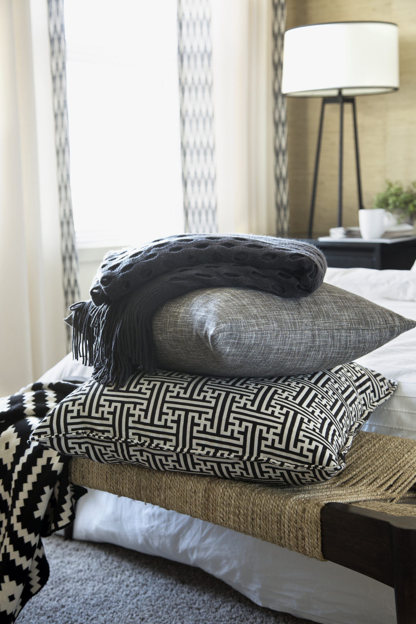 Pillows and blanket stacked on bench in bedroom