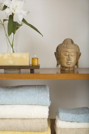 Spa equipments with Buddha sculpture on a shelf